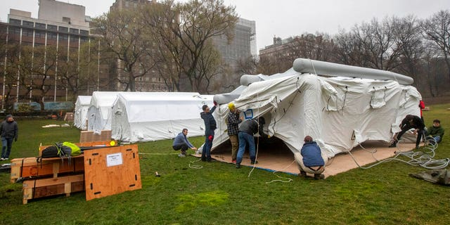 A Samaritan's Purse crew works on building an emergency field hospital equipped with a respiratory unit in New York's Central Park across from the Mount Sinai Hospital in March. (AP Photo/Mary Altaffer)