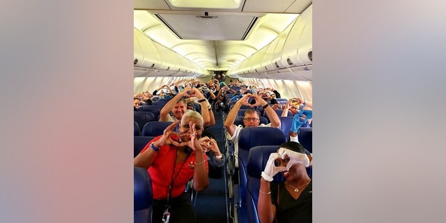 This photo provided by Southwest Airlines employee Dayartra Etheridge shows health care workers, other passengers and flight crew aboard a Southwest flight from Atlanta to New York's LaGuardia Airport holding their hands in the shape of a heart, before the plane pushed back from the gate, at Hartsfield-Jackson Atlanta International Airport.