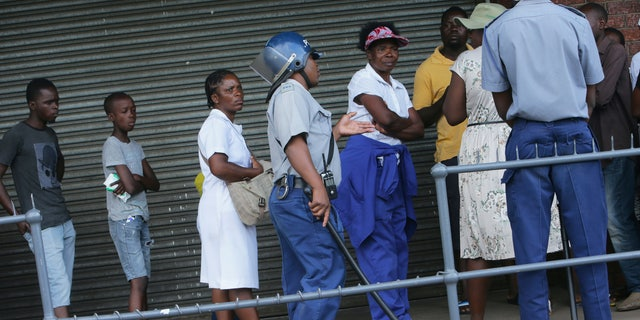 Zimbabwean police urge people to practice social distancing while in a queue to enter a supermarket in Harare, Zimbabwe, Monday, March 30, 2020. Zimbabwe went into lockdown for 21 days in an effort to curb the spread of the coronavirus. The new coronavirus causes mild or moderate symptoms for most people, but for some, especially older adults and people with existing health problems, it can cause more severe illness or death. (AP Photo/Tsvangirayi Mukwazhi)