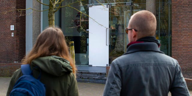Two people look at the glass door which was smashed during a break-in at the Singer Museum in Laren, Netherlands. (AP Photo/Peter Dejong)