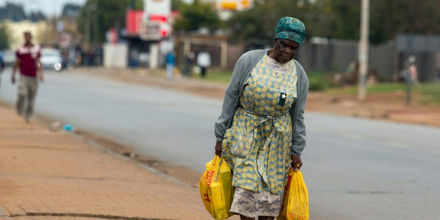 A pensioners Maria Hadebe, walks back home as she carries shopping bags filled with essential items after receiving social grant payout in Thokoza, east of Johannesburg, South Africa, Monday, March 30, 2020, as South Africa continued its nationwide lockdown for 21 days in an effort to control the spread of the coronavirus. The virus causes mild or moderate symptoms for most people, but for some, especially older adults and people with existing health problems, it can cause more severe illness or death. (AP Photo/Themba Hadebe)