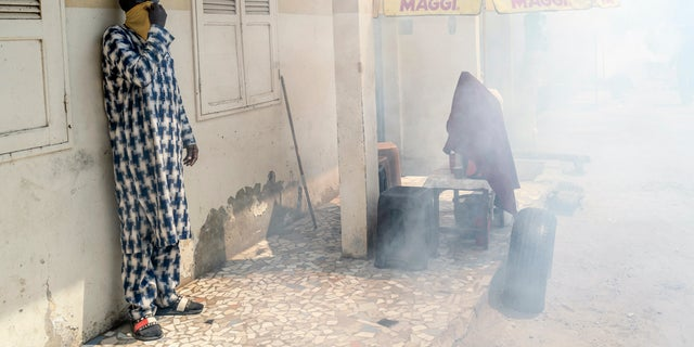 A man uses a cloth to cover his face from the disinfectant being sprayed by a municipal worker in the Grand Market of Dakar, Senegal in an attempt to halt the spread of the new coronavirus Monday, March 30, 2020. The new coronavirus causes mild or moderate symptoms for most people, but for some, especially older adults and people with existing health problems, it can cause more severe illness or death. (AP Photo/Sylvain Cherkaoui)