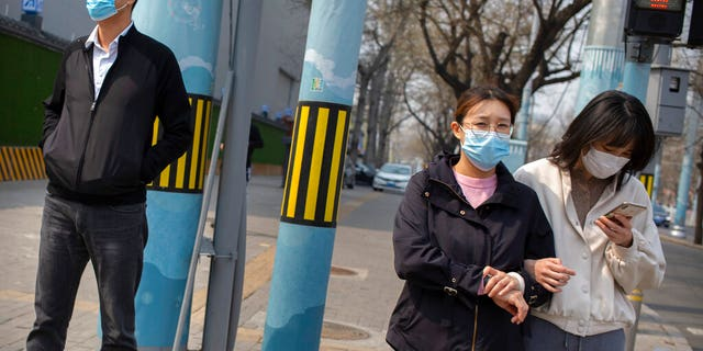 People wearing face masks wait to cross a street in Beijing, Tuesday, March 31, 2020.