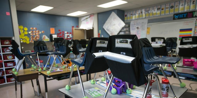 Students' chairs are stacked on top of desks in an empty classroom at closed Robertson Elementary School, March 16, 2020, in Yakima, Wash. (Amanda Ray/Yakima Herald-Republic via AP)