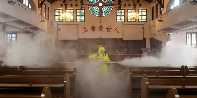 A volunteer sprays disinfectant inside a Christian church in Wuhan in central China's Hubei Province, Friday, March 6, 2020. World stock markets are down sharply again as pessimism prevails over the economic impact of the virus outbreak (Chinatopix via AP)