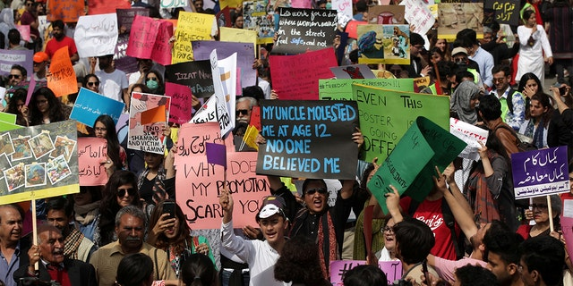 Women and men carry signs as they take part in an Aurat March, or Women's March in Lahore, Pakistan March 8, 2020. REUTERS/Mohsin Raza - RC2QFF9VF0E2