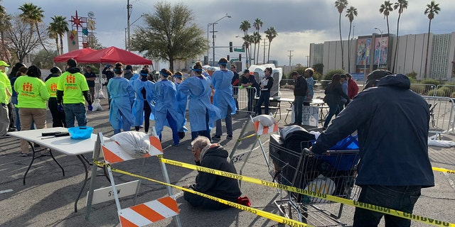 People wait to be screened before entering an homeless shelter set up in a parking lot in Las Vegas on Saturday.