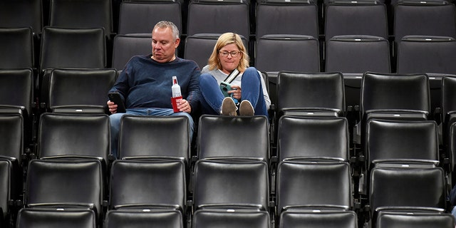 Basketball fans sit in an empty section after it is announced that an NBA basketball game between the Oklahoma City Thunder and Utah Jazz in Oklahoma City has been postponed, Wednesday, March 11, 2020. (AP Photo/Kyle Phillips)