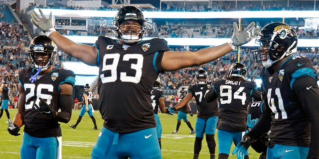 Ex-Jacksonville Jaguars defensive end Calais Campbell (93) celebrates his touchdown against the Indianapolis Colts on a fumble recovery with safety Jarrod Wilson (26) and linebacker Josh Allen (41) during the second half of an NFL football game, in Jacksonville, Fla. On Sunday, March 15, 2020, the Baltimore Ravens agreed to trade a fifth-round draft pick in the upcoming draft to the Jacksonville Jaguars for veteran defensive lineman Calais Campbell. (AP Photo/Stephen B. Morton, File)