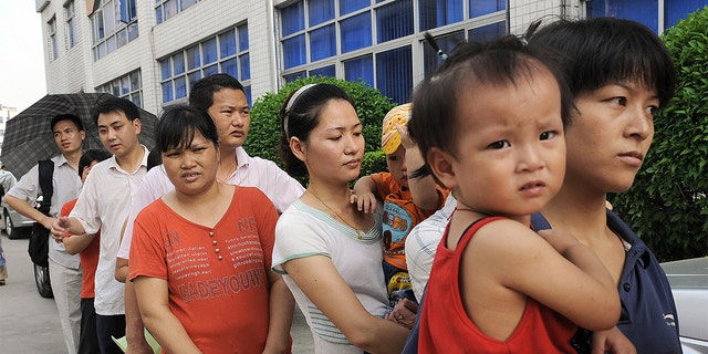 Parents queue up to have their children checked at Longgang central hospital in Shenzhen on Sept. 21, 2008 amidst a tainted milk scandal that killed four babies. (Photo credit should read TED ALJIBE/AFP via Getty Images)