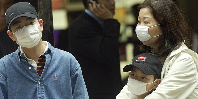 A family wears masks on a street in the Central business district of Hong Kong as the SARS outbreak grips the territory on March 24, 2003. (Photo by Peter PARKS / AFP) (Photo by PETER PARKS/AFP via Getty Images)