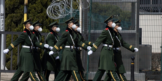 Chinese paramilitary wearing masks march by during their duty in an embassy district in Beijing on Monday, March 16, 2020.