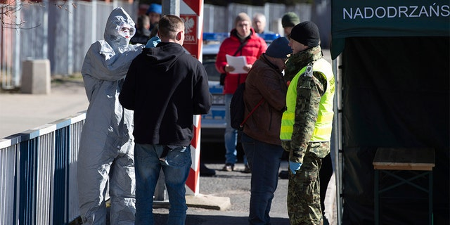 A man in a protective suit checking the body temperature of a man at a Polish border checkpoint on the Bridge of Friendship near Goerlitz, Germany, on Sunday. (Sebastian Kahnert/dpa via AP)