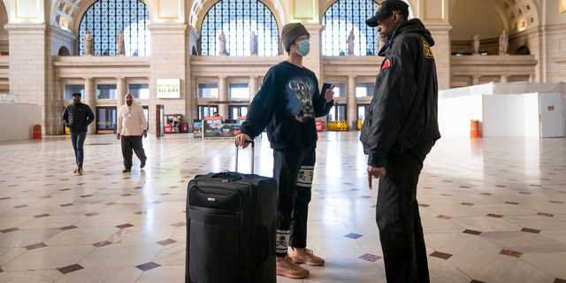 A traveler talks with a security officer at Washington Union Station, a major transportation hub in the nation's capital, Monday, March 16, 2020.