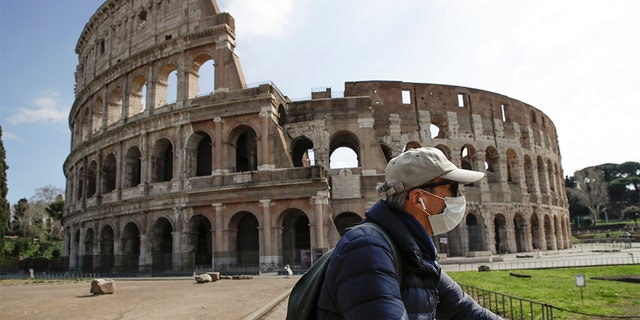 A man wearing a mask rides past the Colosseum in Rome, Sunday, March 15, 2020. Authorities around the world turned to increasingly drastic measures to try to slow the spread of the new coronavirus, with lockdowns, curfews and travel restrictions spreading. For most people, the new coronavirus causes only mild or moderate symptoms. For some, it can cause more severe illness, especially in older adults and people with existing health problems. (AP Photo/Alessandra Tarantino)