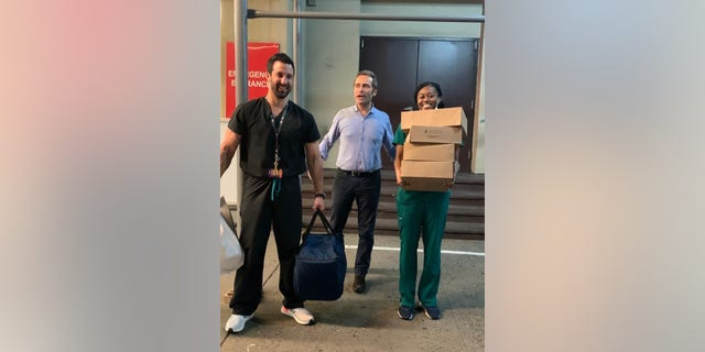 Luca Di Pietro, owner of Tarallucci e Vino, stands with two health-care workers and a stack of donated meals from his restaurant. (Photo courtesy Luca Di Pietro)