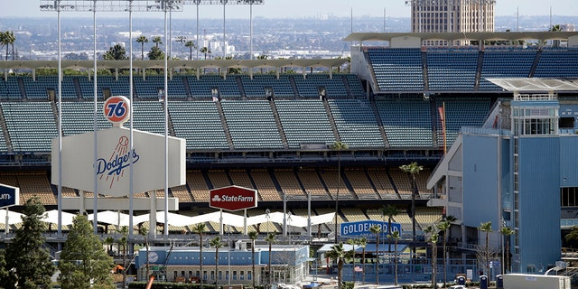 The exterior of Dodgers Stadium, home of the Los Angeles Dodgers is seen Wednesday, March 25, 2020, in Los Angeles. There will be empty ballparks on what was supposed to be Major League Baseball's opening day, with the start of the Major League Baseball regular season indefinitely on hold because of the coronavirus pandemic. (AP Photo/Marcio Jose Sanchez)