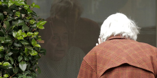 Dorothy Campbell waves while talking through a window to Gene Campbell, her husband of more than 60 years, at the Life Care Center of Kirkland, the long-term care facility linked to several confirmed coronavirus cases in the state, in Kirkland, Washington, U.S. March 5, 2020.