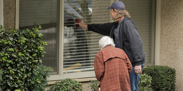 Dorothy Campbell and her son, Charlie Campbell, talk through a window with her husband, Gene Campbell, at the Life Care Center of Kirkland, the long-term care facility linked to several confirmed coronavirus cases in the state, in Kirkland, Washington, U.S. March 5, 2020.