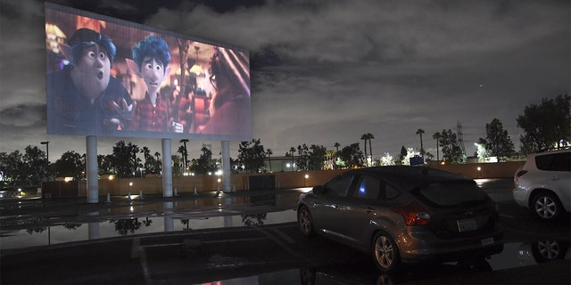 "Viewers in a parked car watch the animated film ""Onward"" at the Paramount Drive-In Theatres, Thursday, March 19, 2020, in Paramount, Calif. The drive-in theater, long a dwindling nostalgia act in a multiplex world, is experiencing a momentary return to prominence. With nearly all of the nation's movie theaters shuttered due to the pandemic, some drive-in owners think they're in a unique position to give moviegoers a chance to do something out of the house but stay within prudent distance from one another. (AP Photo/Chris Pizzello)"
