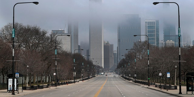 Fog lifts over Chicago and the usually busy Columbus Drive, Tuesday, March 24, 2020, on the second work day since Illinois Gov. J.B. Pritzker gave a shelter in place order last week due to the coronavirus. (AP Photo/Charles Rex Arbogast)