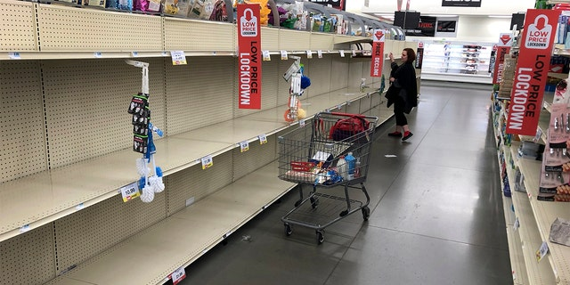 A woman shops among empty shelves at a Hy-Vee food store Friday, March 13, 2020, in Overland Park, Kan. (AP Photo/Charlie Riedel)