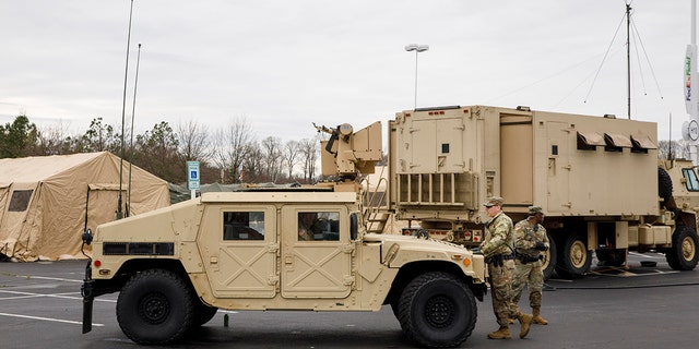 Soldiers with a security unit guard the perimeter as members of the National Guard set up tents to be used for coronavirus testing, Saturday, March 21, 2020, in a parking lot for FedEx Field in Landover, Md., outside of Washington. (AP Photo/Jacquelyn Martin)
