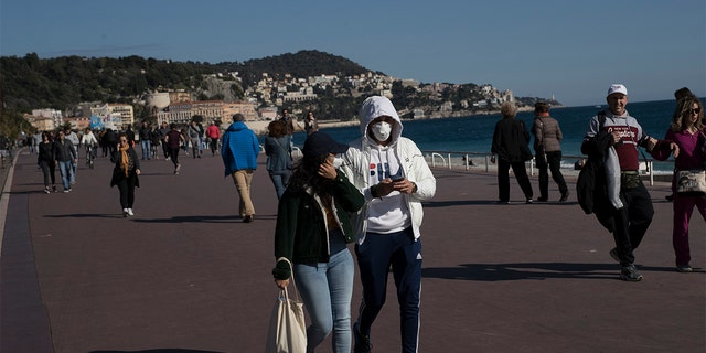 People wearing masks walk along Nice's Promenade des Anglais in Nice, southern France, Sunday, March 15, 2020. (AP Photo/Daniel Cole)