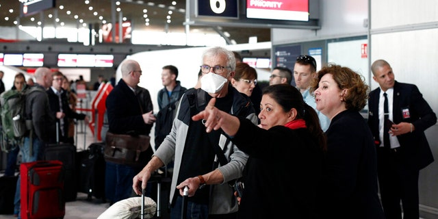 Passengers await flights out of Charles de Gaulle airport, north of Paris, on March 12, 2020, following President Trump's decision to restrict travel from 26 European nations.