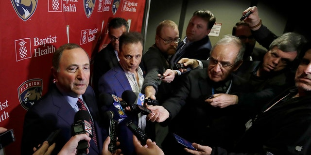 National Hockey League Commissioner Gary Bettman, left, speaks to members of the media , Saturday, March 7, 2020, in Sunrise, Fla. (AP Photo/Wilfredo Lee)