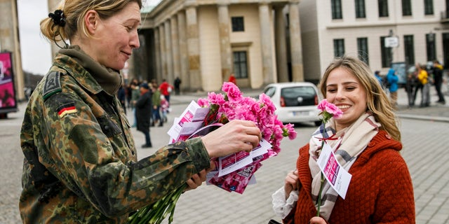 A soldier of the Bundeswehr hands out a carnation to a passerby in front of the Brandenburg Gate on International Women's Day on March 8, 2019 in Berlin, Germany.