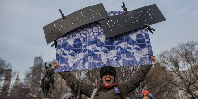 A woman holds a banner during a rally to mark International Women's Day at Union Square on March 08, 2019.