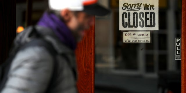 SAN FRANCISCO, CALIFORNIA - MARCH 17: A pedestrian walks by a closed sign on the door of a restaurant on March 17, 2020 in San Francisco, California.  (Photo by Justin Sullivan/Getty Images)