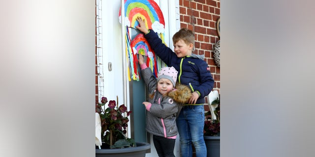 In this March 27 photo, children at home in Moorrege near Hamburg, Germany, hang rainbow artwork outside. (Martin Rose/Getty Images)