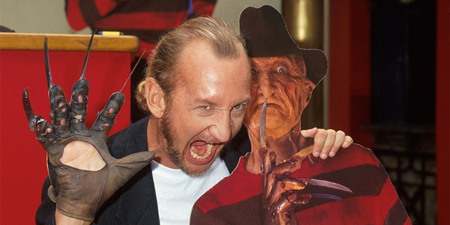 Actor Robert Englund posing with a cardboard cutout of character Freddy Krueger from his film series 'Nightmare on Elm Street.'
