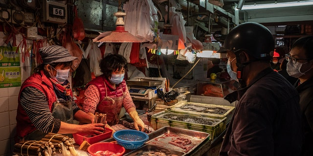 Residents wearing face masks purchase seafood at a wet market on Jan. 28 in Macau, China.