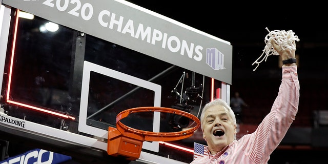 Boise State coach Gordy Presnell holds up the net after Boise State defeated Fresno State to win the Mountain West Conference women's tournament championship. (AP Photo/Isaac Brekken)