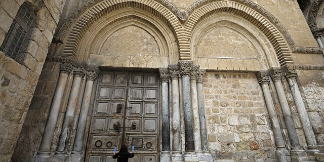A woman prays in front of the Church of the Holy Sepulchre in the Old City of Jerusalem following the closure of the city for non-residents as a measure to contain the spread of the novel coronavirus, on March 30, 2020. (Photo by MENAHEM KAHANA / AFP) (Photo by MENAHEM KAHANA/AFP via Getty Images)