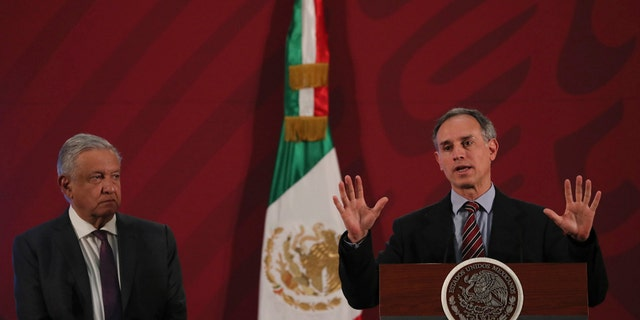 Mexico's President Andres Manuel Lopez Obrador, left, watches his Health Sub Secretary Hugo Lopez speak about hand washing as one of the ways to help prevent the spread of the new coronavirus during the president's daily news conference in Mexico City, early Thursday, March 19, 2020. (AP Photo/Fernando Llano)