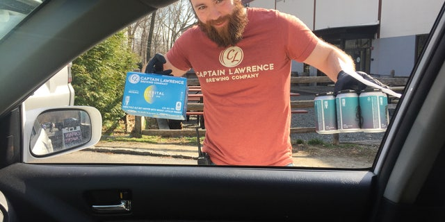 Rob, an employee of Captain Lawrence Brewing Co. in Elmsford, New York, makes a curbside no-contact drink delivery while wearing rubber gloves as part of the brewery's coronavirus precautions, and efforts to stay afloat during the statewide shutdown.Capt. Lawrence is using brewing equipment to make hundreds of gallons of chicken soup for a local food industry worker charity.