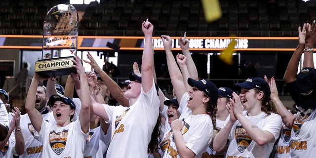 Members of the IUPUI team hoist the trophy after they defeated Green Bay 61-37 in an NCAA college basketball game for the Horizon League women's tournament championship in Indianapolis, Tuesday, March 10, 2020. (AP Photo/Michael Conroy)