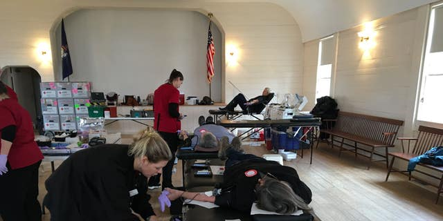 Donors give blood at an American Red Cross blood drive in Boothbay, Maine during the Coronavirus pandemic