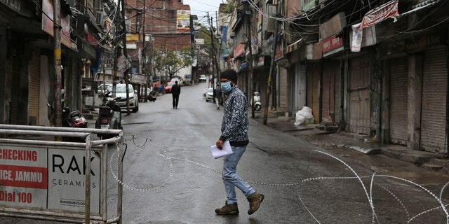 An Indian man wearing a mask walks past a barbed wire erected by authorities as part of enforcing a lockdown as a precautionary measure against COVID-19 in Jammu, India, Tuesday, March 24, 2020.