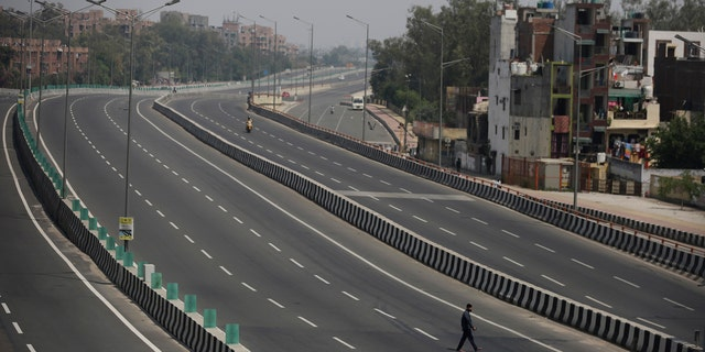 A man crosses an empty expressway during a complete lockdown amid growing concerns of coronavirus in New Delhi, India, Tuesday.