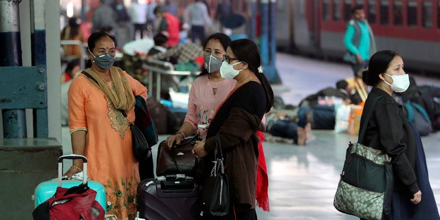 Indian passengers wearing masks as a precaution against the new coronavirus wait at railway station in Jammu, India, Tuesday, March 17, 2020.