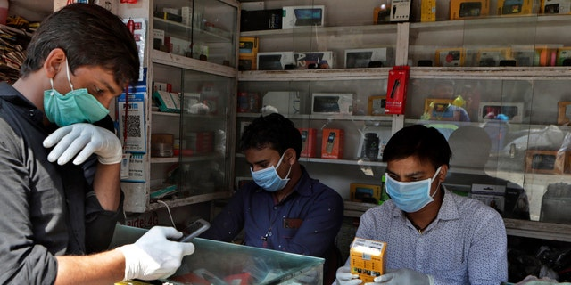 Indian mobile vendors wear protective masks and gloves as a precaution against a new virus at their outlet in Mumbai, India, Tuesday, March 17, 2020.