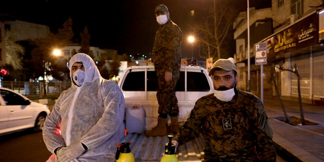In this Wednesday, March 4, 2020, photo, Revolutionary Guard members take part in disinfecting the city to help prevent the spread of the new coronavirus in Tehran, Iran. Wearing gas masks and waterproof fatigues, members of Iran's Revolutionary Guard now spray down streets and hospitals with disinfectants as the Islamic Republic faces one of the world's worst outbreaks of the new coronavirus. (AP Photo/Ebrahim Noroozi)