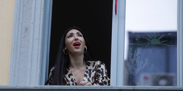 Opera singer Laura Baldassari leans out of her window to sing during a flash mob launched throughout Italy to bring people together and try to cope with the emergency of coronavirus, in Milan, Italy, Friday, March 13, 2020. Italians have been experiencing yet further virus-containment restrictions after Premier Giuseppe Conte ordered restaurants, cafes and retail shops closed after imposing a nationwide lockdown on personal movement. For most people, the new coronavirus causes only mild or moderate symptoms. For some it can cause more severe illness. (AP Photo/Luca Bruno)