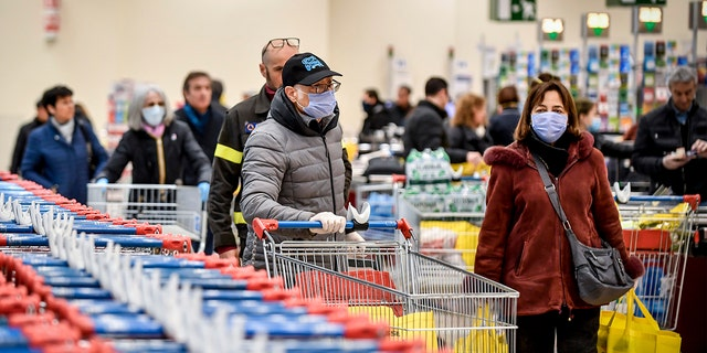 People wearing masks at a supermarket in Milan on Sunday. (Claudio Furlan/LaPresse via AP)