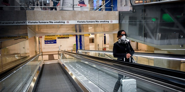 A woman wearing a mask on an escalator inside Milan's central train station Sunday. (Claudio Furlan/LaPresse via AP)